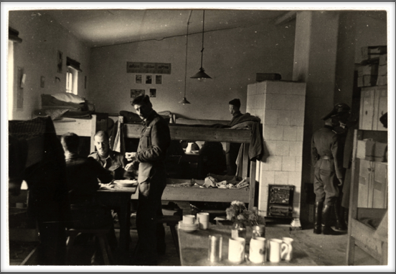 1942-43 inside barracks, porcelain stove visible on the right, barracks bunks and general layout
