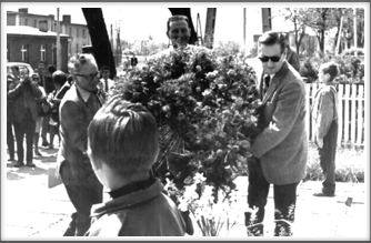 Charlie Eberle, John Slack, and Frank Maxwell laying a large wreath at the Flame Memorial on the site  of Oflag 64