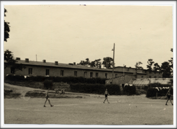 October 7, 1944 American POWs on the sports ground with barracks in the background and greenhouse on the right