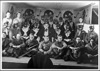 "November '43 - Glee Club, ""The Robert E. Lee Minstrels"", First Row l-r:  T. A. Mitchell, J. Barker, R. Chappell, F. Saxton, K. Goddard, J. Van Vliet, H. Littman.  Second Row l-r: T. Cipriani, B. Fabian, T. Holt, K. Willis, H. Holder, C. Campbell, F. Maxwell, S. Thal, W. Sharpe.  Standing l-r: R. Ford, L. Farber, J. Cockrell and other members of the cast and orchestra."