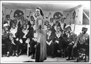 "November '43 - Glee Club, ""The Robert E. Lee Minstrels"", Leo Farber as ""Queenie"".  Front Row l-r:  B. Fabian, T. Holt, K. Willis, H. Holder, C. Campbell, F. Maxwell, S. Waldman, W. Sharpe,  Second Row l-r:  Davis, D. Waful, Jones, Carlson, S. Bolten.  Third Row l-r:  Crawford, Carlson, Fraser, Bolten, Johnson"