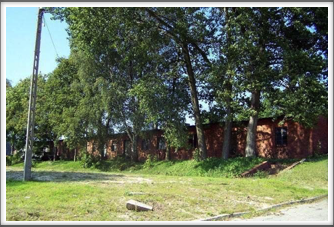 This is the only barracks left. The others have been burned or destroyed. It is in back of and nearly far left from the hospital.