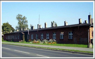 Former barracks across the street from Oflag 64, where the Germans were billeted. Note the dog in front of the building.