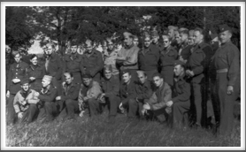 Unknown date, Oflag 64 group photo taken just outside of camp. (right view) Kneeling, l-r:  3rd, Tony Cipriani; 4th, Otto Amerell; 5th, Roy Chappell; 6th, Everette Anderson; 9th, Major Hugo Fielschmidt; Standing middle row l-r: 3rd, William Harlow; 4th, Nick Rahal; 6th, Billy Bingham; 7th, Lou Otterbein; 9th, Robert Henry, Jr.; far right, Col. Thomas Drake