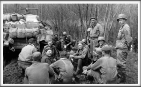 After Liberation, 4/13/45 - Boo Nunnally, sitting just below the B16 marker on the vehicle.  Patrick Ward, just over Boo's left shoulder being handed a cup. Thomas Morton, middle with a spoon in his left hand. Carl Hansen, in front of Boo wearing glasses.